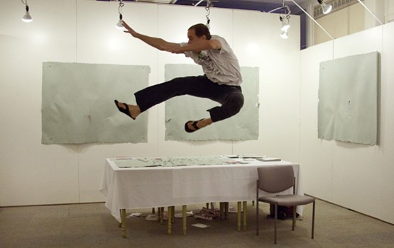 "Thomas Gokey executes a jump kick in a gallery, in front of three panels from his art piece, ""Total Amount of Money Rendered in Exchange for a Masters of Fine Arts Degree to the School of the Art Institute of Chicago, Pulped into Four Sheets of Paper."" Photo courtesy of Thomas Gokey."
